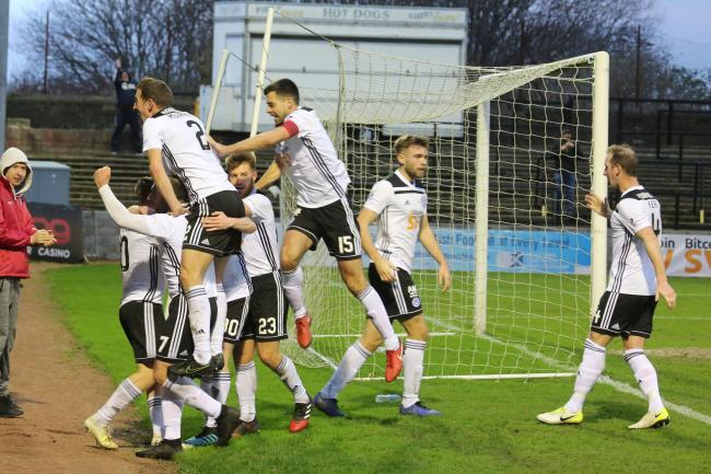 Ayr United players celebrate as Stephen Kelly scores the winner.