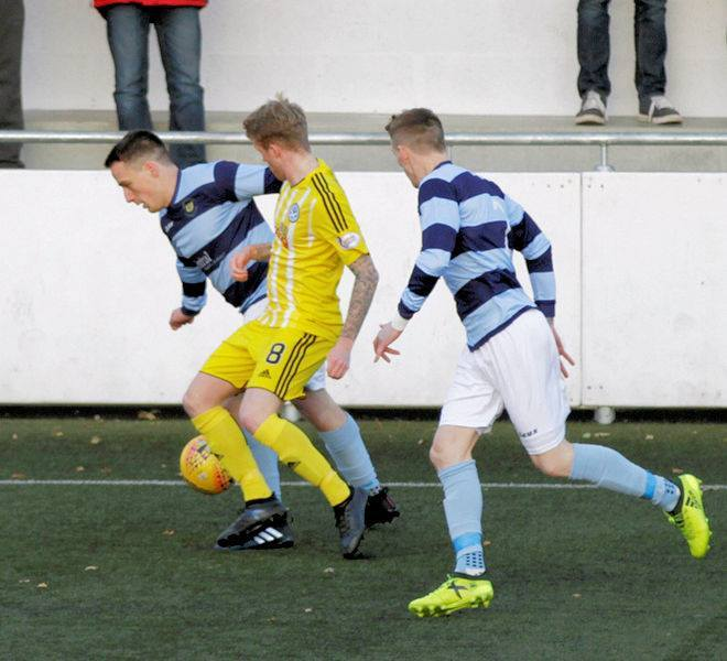 UNDER PRESSURE: Ayr midfielder Robbie Crawaford battles for the ball with two opponents. Picture: Iain Robb.