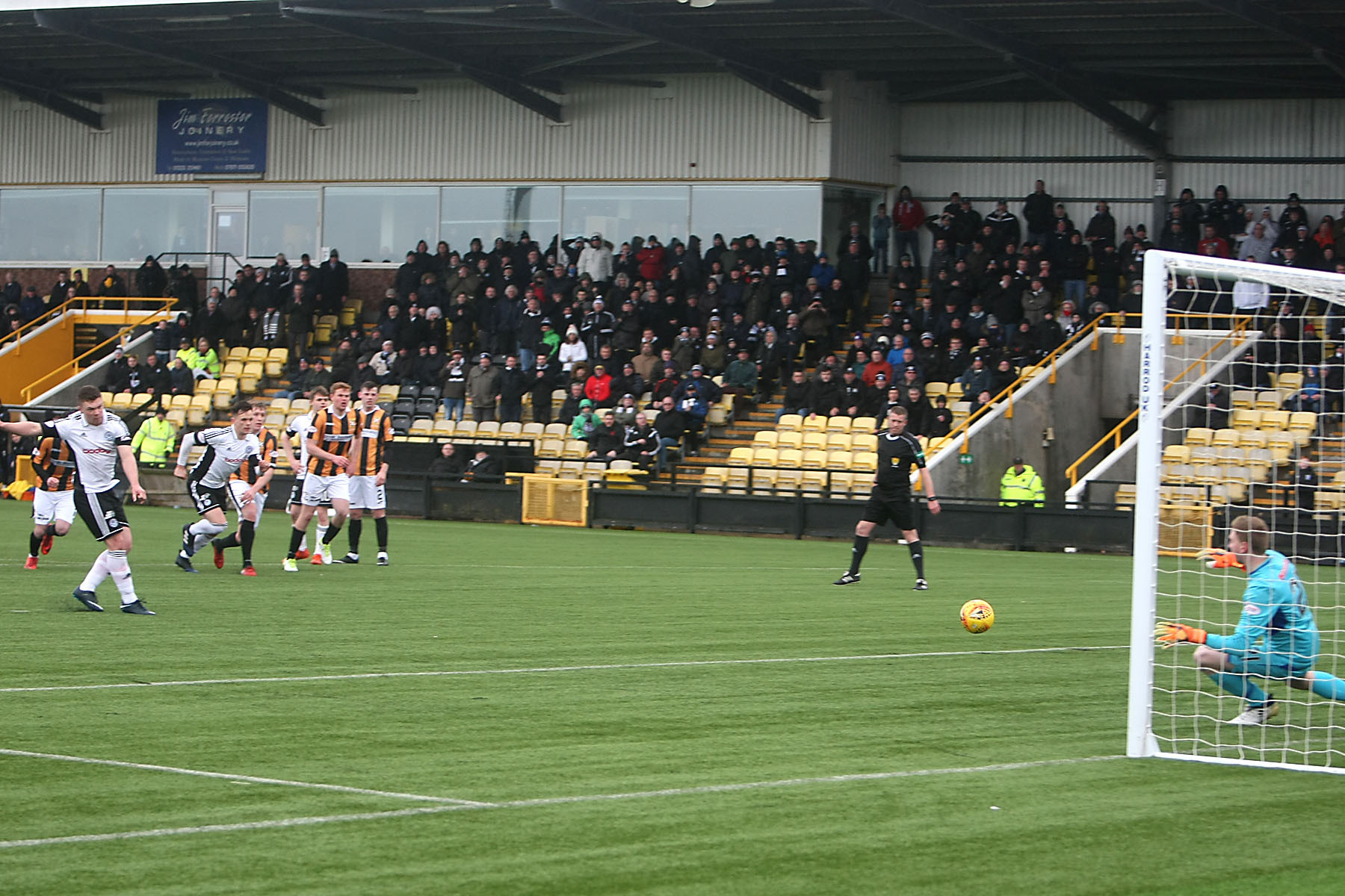 SPOT ON: Craig Moore fires home a late penalty kick to win the match for the visitors.